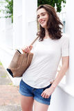 Jeune femme attirante avec la bourse et penchement contre la barrière photo stock