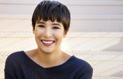 Jeune femme attirante avec le sourire amical de cheveux élégants courts images stock
