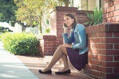 Jeune femme attirante avec le téléphone sur la rue ensoleillée Image stock