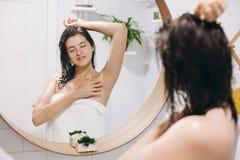 Jeune femme attirante avec les cheveux humides en serviette blanche appréciant la peau lisse après le rasage des aisselles, réfle image libre de droits