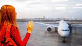 Jeune femme attirante avec les cheveux rouges et les verres regardant des avions sur l'aéroport de piste Photographie stock libre de droits