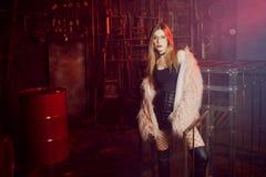 Jeune femme attirante avec les vêtements élégants Belle fille dans le manteau de fourrure rose pelucheux, fond de Cyberpunk Lampe Image stock