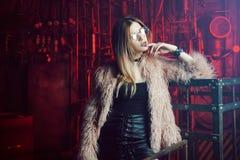 Jeune femme attirante avec les vêtements élégants Belle fille dans le manteau de fourrure rose pelucheux, fond de Cyberpunk Lampe Images libres de droits