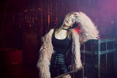Jeune femme attirante avec les vêtements élégants Belle fille dans le manteau de fourrure rose pelucheux, fond de Cyberpunk Lampe Photographie stock