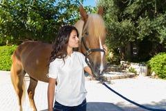 Jeune femme attirante avec son cheval aux écuries Photographie stock libre de droits
