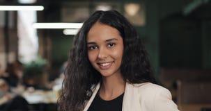 Jeune femme attirante avec un smartphone examinant la sensation de sourire de caméra heureuse en café confortable banque de vidéos