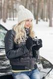 Jeune femme attirante avec un vieil appareil-photo près de la voiture noire Photographie stock libre de droits