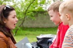 Jeune femme attirante causant à deux petits garçons Images stock
