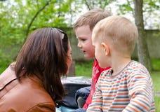 Jeune femme attirante causant à deux petits garçons Photographie stock libre de droits