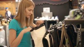 Jeune femme attirante choisissant des sacs à la boutique Faisant des emplettes dans le mail, temps de ventes Concept de consommat banque de vidéos