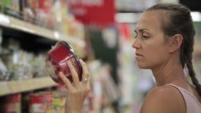 Jeune femme attirante choisissant la nourriture rapide à préparer au supermarché clips vidéos