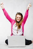 Jeune femme attirante célébrant avec l'ordinateur portatif Image stock