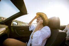 Jeune femme attirante conduisant dans le cabriolet au bord de la mer photographie stock libre de droits