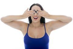 Jeune femme attirante couvrant ses yeux tirant des visages Photos stock