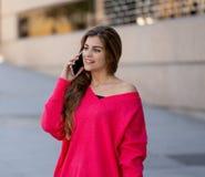Jeune femme attirante d'étudiant parlant et causant à son téléphone intelligent dehors dans une ville européenne images stock