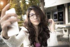 Jeune femme attirante d'affaires s'asseyant en café et employant le mobile photographie stock libre de droits