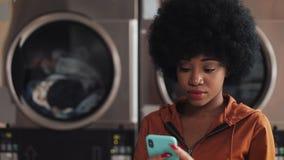 Jeune femme attirante d'Afro-am?ricain ? l'aide du smartphone se reposant dans la blanchisserie publique de libre service Elle es banque de vidéos