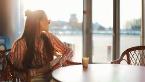 Jeune femme attirante dans des lunettes de soleil rouges avec la tablette se reposant en café Belle fille dans l'aéroport ou shop banque de vidéos