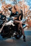 Jeune femme attirante dans l'équipement en cuir noir avec la moto classique de style photographie stock