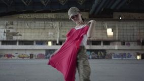 Jeune femme attirante dans l'uniforme militaire essayant sur la robe rouge et dansant autour, souriant dans le bâtiment abandonné banque de vidéos