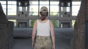 Jeune femme attirante dans l'uniforme militaire marchant lentement dans le bâtiment abandonné sale poussiéreux Femme de guerrier  banque de vidéos