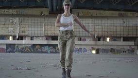 Jeune femme attirante dans l'uniforme militaire marchant sur le plancher en béton dans le bâtiment abandonné sale poussiéreux ver banque de vidéos