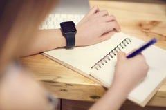 Jeune femme attirante dans la montre intelligente de frome de note de bureau sur le bureau Photographie stock libre de droits