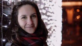 Jeune femme attirante dans la neige en baisse la nuit Noël regardant l'appareil-photo tenant le mur proche de lumières, Photographie stock libre de droits