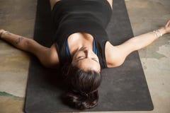 Jeune femme attirante dans la pose de cadavre, fond de plancher de studio Photos stock