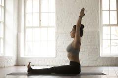 Jeune femme attirante dans la pose de Dandasana, dos blanc de studio de grenier photo libre de droits