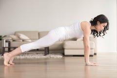 Jeune femme attirante dans la pose de planche au salon confortable Photos stock