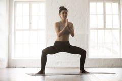 Jeune femme attirante dans la pose de posture accroupie de sumo, studio blanc de grenier image stock