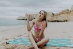 Jeune femme attirante dans le bikini avec le corps parfait détendant sur un sable à la belle plage avec des roches photo libre de droits