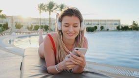 Jeune femme attirante dans le bikini rouge et la musique de écoute d'écouteurs blancs de son smartphone, chanson de chant tout en banque de vidéos