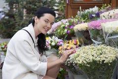 Jeune femme attirante dans le fleuriste d'extérieur Photos stock