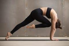 Jeune femme attirante dans le genou à la pose de boucle de front, studio Photographie stock libre de droits