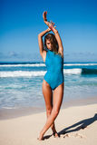 Jeune femme attirante dans les vêtements de bain posant sur la plage sablonneuse pendant la journée Photos libres de droits