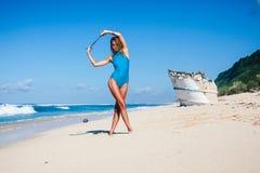 Jeune femme attirante dans les vêtements de bain posant sur la plage sablonneuse pendant la journée Images stock