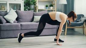 Jeune femme attirante dans les vêtements de sport formant à la maison étirer des jambes sur le plancher banque de vidéos