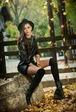 Jeune femme attirante dans un tir automnal, dehors Belle fille à la mode avec l'équipement moderne posant se reposer en parc Image stock