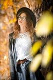 Jeune femme attirante dans un tir automnal dehors Belle fille à la mode d'école posant en parc avec les feuilles fanées autour Photographie stock