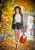 Jeune femme attirante dans un tir automnal dehors Belle fille à la mode d'école posant en parc avec les feuilles fanées autour Photo stock