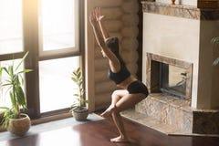 Jeune femme attirante dans une pose à jambes de chaise, intérieur de maison Image libre de droits
