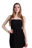Jeune femme attirante dans une robe noire souriant et regardant c Photographie stock libre de droits