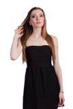 Jeune femme attirante dans une robe noire souriant et regardant c Photos stock