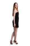 Jeune femme attirante dans une robe noire souriant et regardant c Image stock