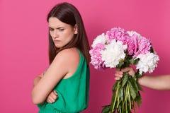 Jeune femme attirante de brune avec le visage fronc? les sourcils tournant ? partir des fleurs, se tenant d'isolement au-dessus d photographie stock libre de droits