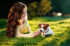 Jeune femme attirante de brune jouant avec son chien en parc vert à l'été, concept de personnes de mode de vie Image stock