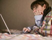 Jeune femme attirante de brune se trouvant sur le lit et travaillant dans son ordinateur portable photos stock