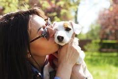 Jeune femme attirante de hippie dans des lunettes de soleil embrassant le chiot de terrier de Russell de cric au parc, à la pelou Photos libres de droits
